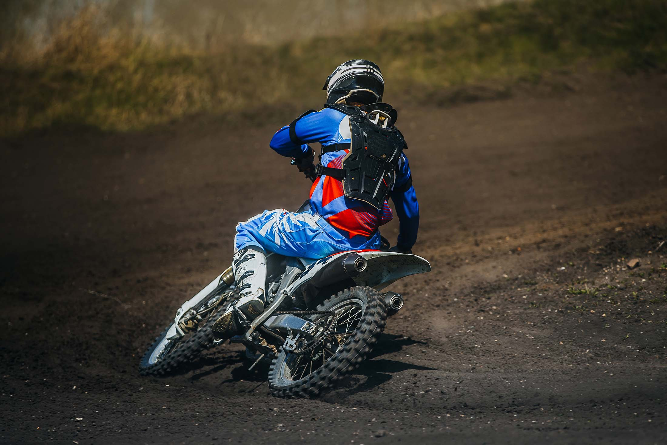 motorcycle racer on a motorcycle rides in turn a dusty track during competition racing